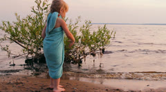 Little girl plays in sand on the bank of a reservoir Stock Footage