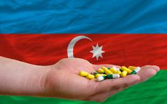 Stock Photo of holding pills in hand in front of azerbaijan national flag