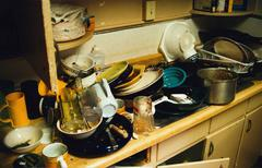 Dirty dishes piled in a sink Stock Photos