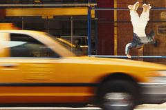 Boy doing gymnastics, taxi drives by Stock Photos