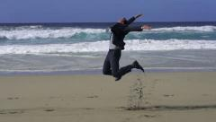 Businessman jumping on the beach, slow motion shot at 480fps Stock Footage