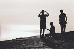 three people in silouette standing on a cliff over the ocean - stock photo
