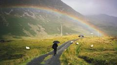 rainbow over a rural road where a person walks with an umbrella - stock photo