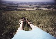 Stock Photo of a woman's legs and feet outstretched in grass overlooking fields