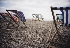 Lounge chairs being blown by the wind on a beach Stock Photos