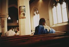 Peopled sitting in pews inside a church Stock Photos