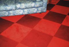 Part of a blue, flowery couch on a red-checkered floor Stock Photos
