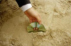 A man retrieving a compact disc from sand Stock Photos