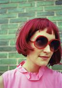 A woman with bright pink hair, pink shirt, and red sunglasses Stock Photos