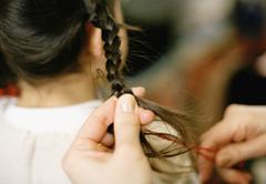 Woman braiding girl's hair Stock Photos