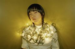 A young woman looking forward, wrapped in Christmas lights Kuvituskuvat