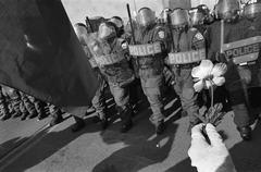 A line of riot police and a person holding a flower Stock Photos