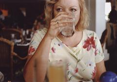 A mature adult woman drinking Stock Photos
