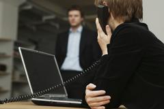 Nainen istuu pöydän ääressä, joka käyttää kannettavaa kun puhut puhelimitse Kuvituskuvat