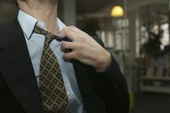 A man in a suit tugging at his collar Stock Photos
