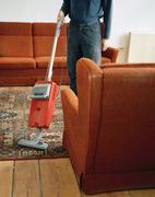 A person vacuuming a rug Stock Photos