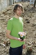 Stock Photo of A young man holding flowers