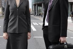 A businessman and a businesswoman standing in a city street Stock Photos