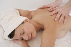 A massage therapist massaging a woman's back Stock Photos