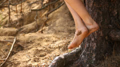 Naked legs of a girl, pretty girl in swimsuit sitting in the tree by the sea Stock Footage