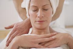 A massage therapist massaging a woman's neck Stock Photos