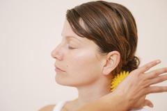 Stock Photo of A woman massaging her neck with a massage ball