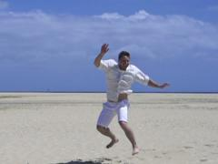 Young man in white clothes jumping on the beach, slow motion shot at 120fps Stock Footage