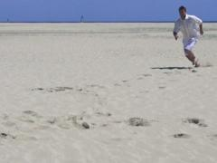 Man in white clothes runinng to the camera on the beach, slow motion 480fps Stock Footage