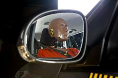 A crash test dummy reflected in a side-view mirror Stock Photos
