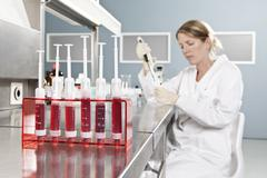 A row of vials holding blood and a lab technician working in background, focus Stock Photos