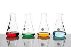 Four conical flasks holding different colored fluids - stock photo