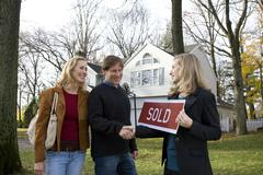 Real estate t shaking hands with a couple - stock photo