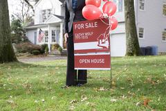 A real estate t standing by a FOR SALE sign Stock Photos