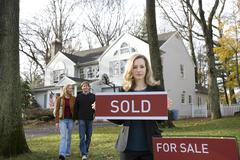 A real estate t holding a SOLD sign Stock Photos