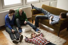 Four teenage friends hanging out in a living room - stock photo