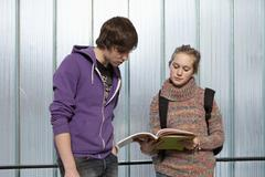 A teenage boy and girl looking at a school workbook together - stock photo