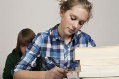A teenage girl doing class work, boy in background - stock photo