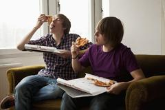 Two boys eating delivery pizza - stock photo