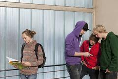 Three teenage boys looking at a mobile while ignoring a teenage girl in a school Stock Photos