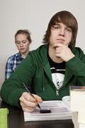 A teenage boy thinking in a classroom, girl in background - stock photo