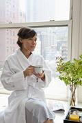 A woman wearing a bathrobe sitting on a window sill and holding a mug, looking Stock Photos