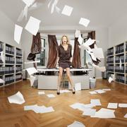 A woman standing in an office while sheets of paper blow around the room Stock Photos