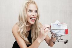 Stock Photo of A woman holding a miniature shopping trolley containing European Union bank