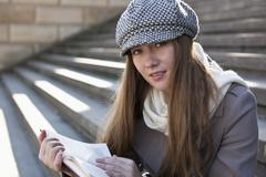 Woman on steps outside reading - stock photo