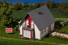 A diorama of a miniature house with a  ZU VERKAUFEN (for sale in German) sign Stock Photos