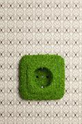 Energy saving electrical wall outlet covered in grass Stock Photos