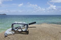 A diving mask and snorkel on a rock near the sea Stock Photos