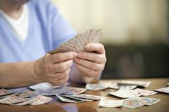 A senior woman playing cards, midsection, focus on hands - stock photo