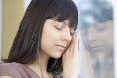 A woman with her eyes closed leaning against a window - stock photo