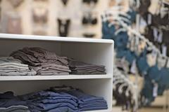 Folded t-shirts in a clothing store Stock Photos